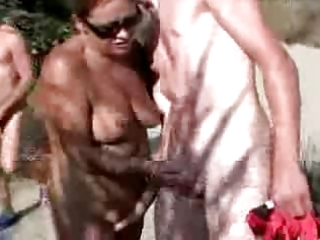 68 years old wife with youthful lad in the beach